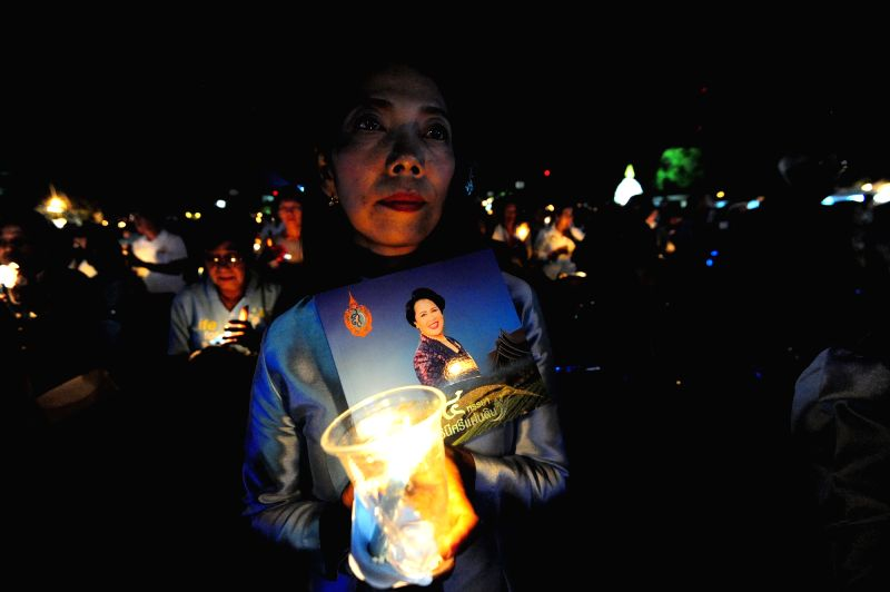 BANGKOK, Aug. 13, 2017 - A well-wisher prays for the health of Queen Sirikit, the Queen Dowager of Thailand, during a candle-lighting ceremony at the Dusit Palace Plaza in Bangkok, Thailand, Aug. 12, ...