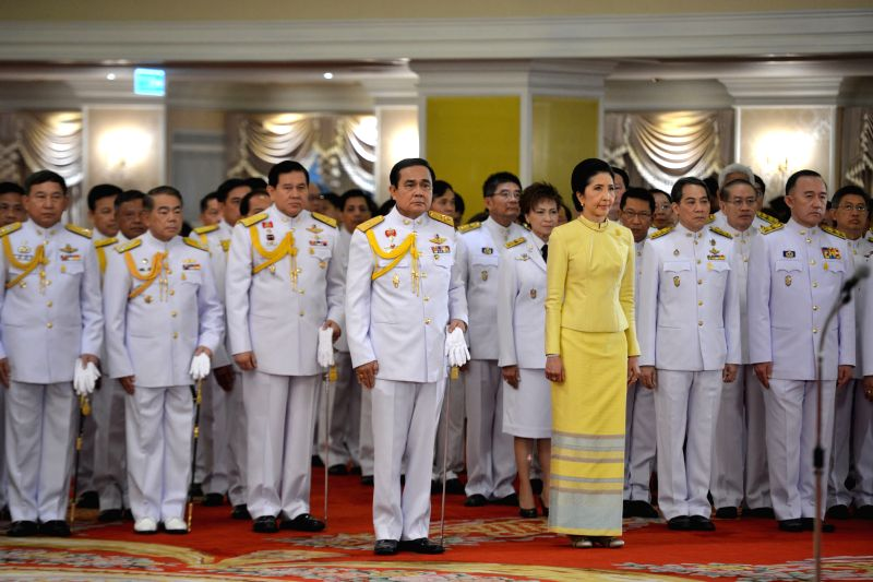 Thai junta chief Prayuth Chan-ocha (L Front) stands before receiving a royal command formally appointing him the 29th prime minister of the country, on Aug. 25, ...