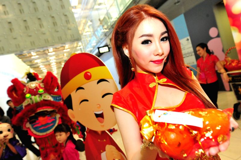 A woman holds oranges during an event to welcome Chinese tourists and celebrate Chinese Lunar New Year at Suvarnabhumi Airport in Bangkok, Thailand, Feb. 19, 2015. ...