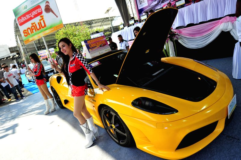 Models present seized luxury cars during an auction at Thai Customs headquarters in Bangkok, Thailand, Feb. 27, 2015. 232 seized luxury cars were auctioned on ...