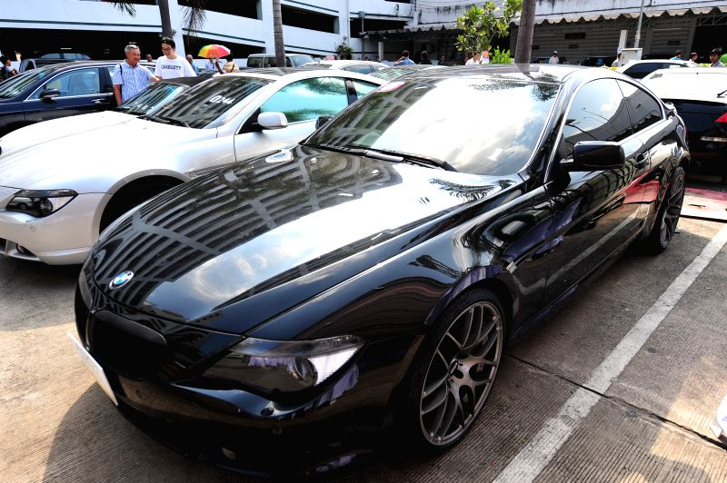 Thai people look at seized luxury cars during an auction at Thai Customs headquarters in Bangkok, Thailand, Feb. 27, 2015. 232 seized luxury cars were auctioned on ...