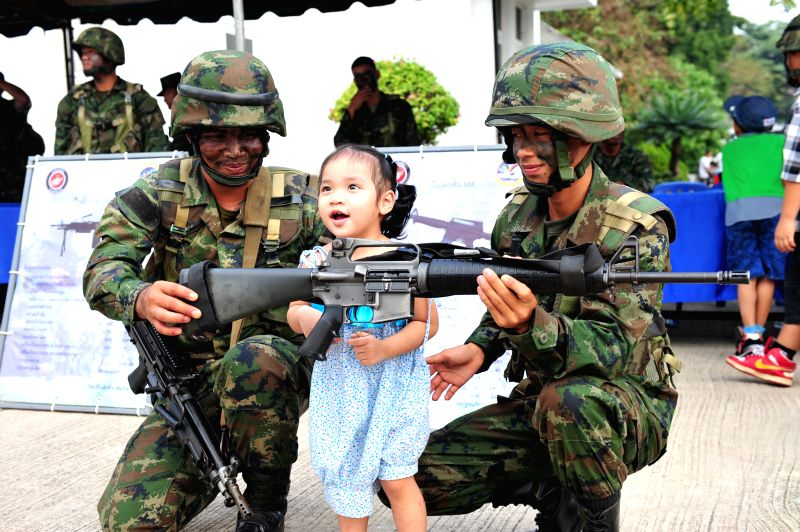 A child touches a machine gun on Children's Day at the Royal Thai Navy Academy in south Bangkok, Thailand, Jan. 10, 2015. The Thai National Children's Day is ...