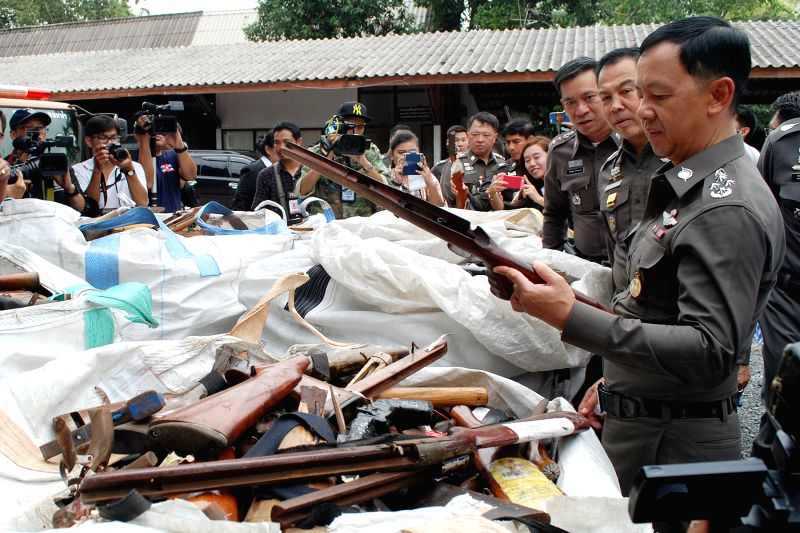 Acting National Police Chief Gen. Watcharapol Prasarnrajkit (1st R) looks at an old rifle on display before being destroyed at a police weaponry office in Bangkok, .