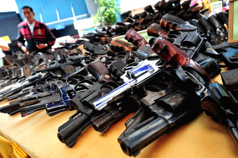 A Thai policeman stands in front of displayed seized guns to be destroyed at Ironworks factory near Bangkok, Thailand, July 15, 2014. All together 34,350 guns that .