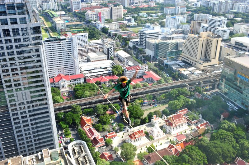 Slackliner Andy Lewis of the U.S. balances himself and walks on a 169 meters (555 feet)-long slackline in Bangkok, Thailand, July 23, 2014. (Xinhua/Rachen ...