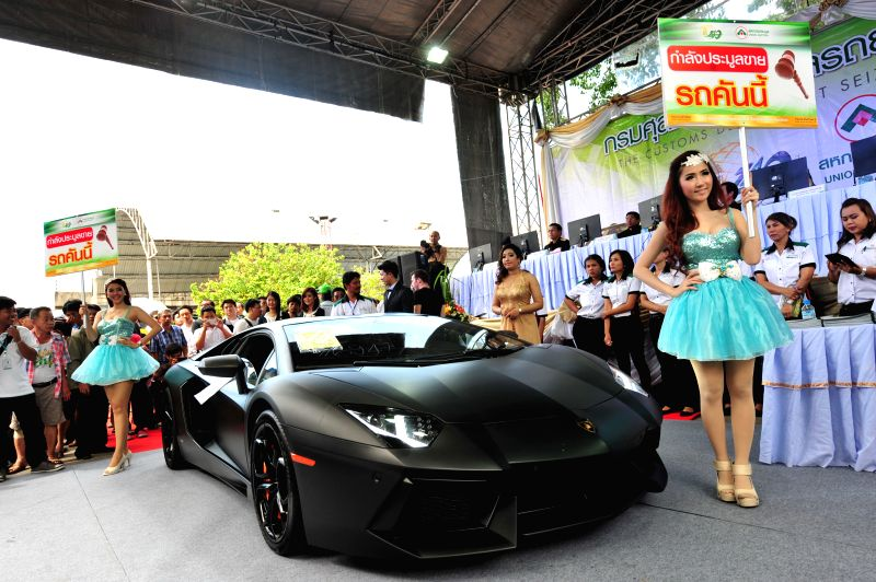 People attend an auction of smuggled cars at Thai Customs Department in Bangkok, Thailand, July 3, 2014.