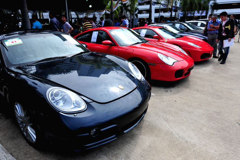 People look at smuggled cars during an auction at Thai Customs Department in Bangkok, Thailand, July 3, 2014.