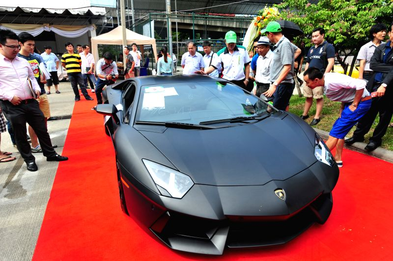 People look at a smuggled car during an auction at Thai Customs Department in Bangkok, Thailand, July 3, 2014.