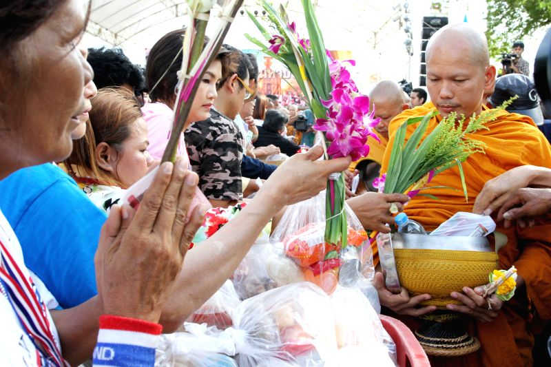 Thai anti-government protesters offer food to Thai Buddhist monks as they mark the Visakha Bucha day during a rally outside the United Nations office near the ...