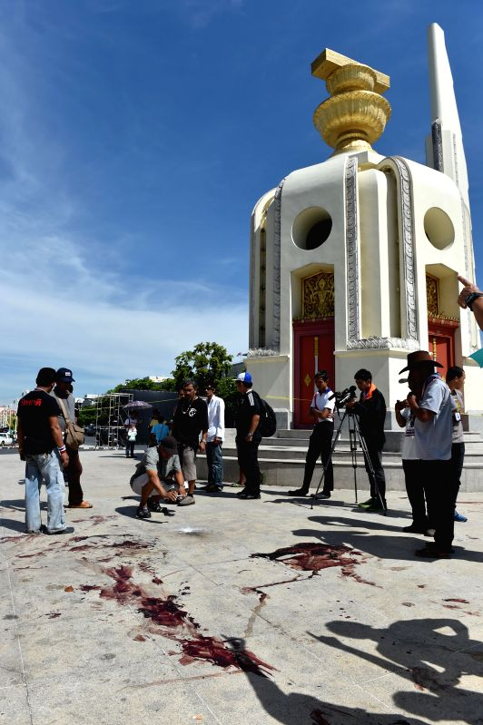 People look at the blood stains at the site of an attack near the Democracy Monument in Bangkok, Thailand, May 15, 2014. Two anti-government protestors were killed ..