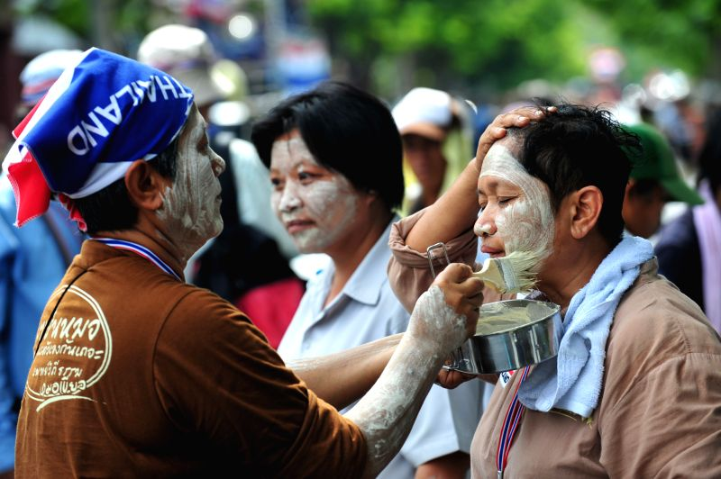 A Thai anti-government protester puts powder on the other's face to protect from heavy sunlight during a rally in front of the Parliament House as senators debate to