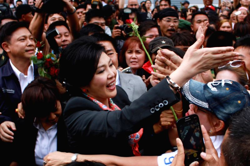 Thai caretaker Prime Minister Yingluck Shinawatra (C) greets supporters after a press conference in Bangkok, Thailand, May 7, 2014. Thailand's Constitutional Court on
