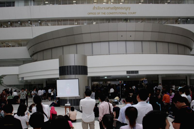 Thai people wait outside the Constitutional Court for news on Yingluck's abuse of power case in Bangkok, Thailand, May 7, 2014. Thailand's Constitutional Court on ...