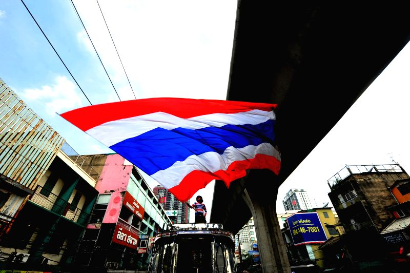 An anti-government protester waves national flag during a rally on main street in Bangkok, Thailand, May 8, 2014.