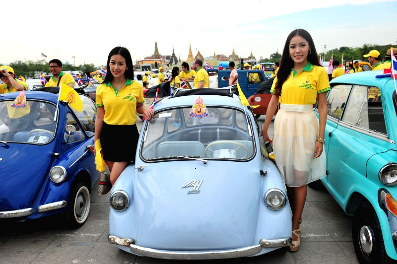 Bangkok (Thailand): People pose for photos with antique cars during a parade as part of the celebration of Thai King's 87th Birthday Anniversary in front of Grand Palace in Bangkok, Thailand, Dec. 4,