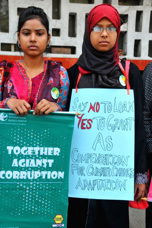 Bangladeshi people holding placards attend a rally during a campaign to welcome the International Anti-Corruption Day at Dhaka University in Dhaka, Bangladesh, Dec. 9, ...