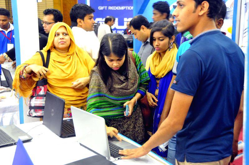 Bangladeshis look at laptops during a laptop fair at Bangabandhu International Conference Centre in Dhaka, Bangladesh, Nov. 13, 2015. A three-day laptop carnival, ...