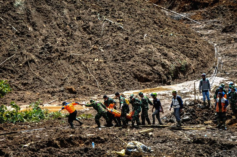 Rescuers carry a dead body at Sampang village in Banjarnegara, Indonesia, Dec. 15, 2014. A landslide hitting the village of Sampang in Banjarnegara of Indonesia on Friday has buried ...