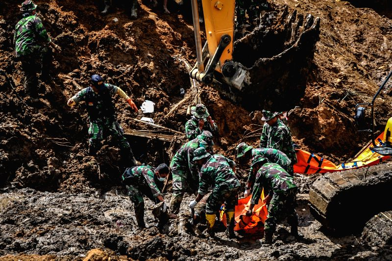 Soldiers recover a dead body as an escavator dredges mud hoarding a road at Sampang village in Banjarnegara, Indonesia, Dec. 15, 2014. A landslide hitting the village of Sampang in ...