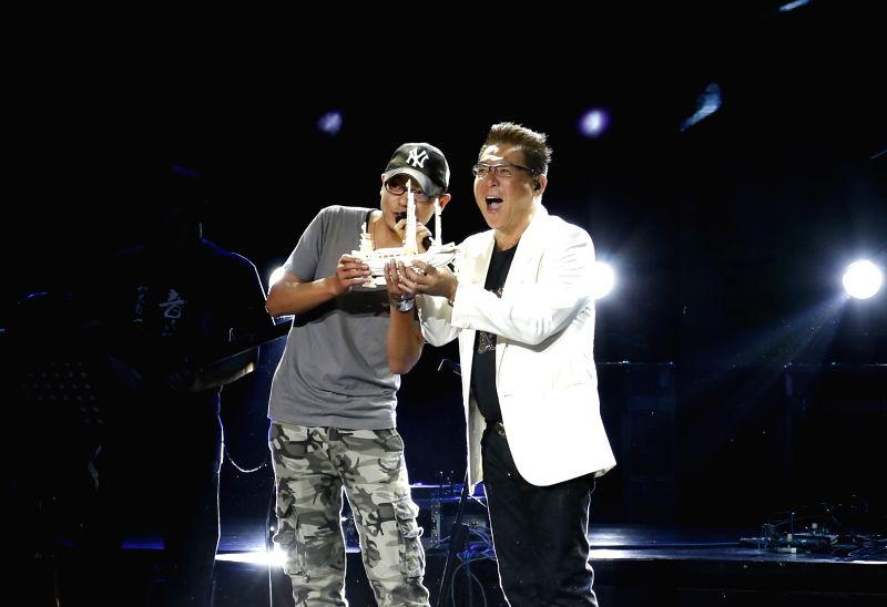 Singer Johnny receives a gift from his fan during his solo concert in Baotou, north China's Inner Mongolia Autonomous Region, June 15, 2014.