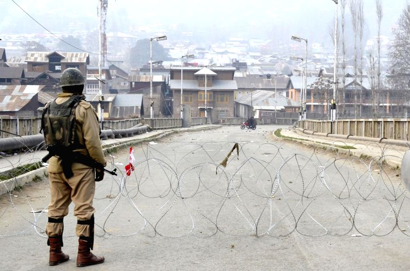 A soldier stands on a stone strewn road after local youths pelted stones on the security forces in Baramulla during the third phase of Jammu and Kashmir assembly polls on Dec 9, 2014.