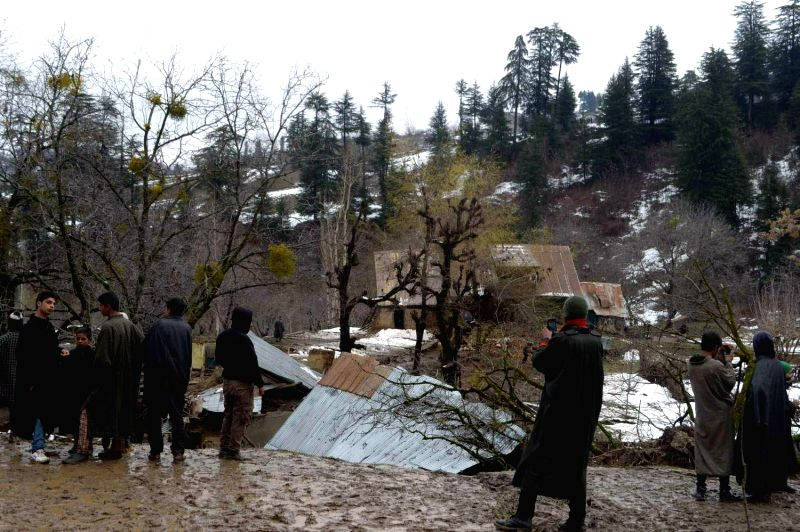 People look at the damage caused by the recent rain and snowfall  in Laridoora village of Jammu and Kashmir's Baramulla on March 17, 2015. Seven houses were damaged in the landslides.