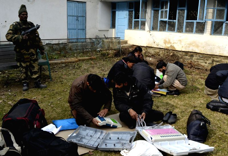 Polling officials prepare for the third phase of Jammu and Kashmir assembly polls under tight security cover at a Baramulla college on Dec 8, 2014.