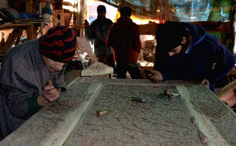 Youths busy carving wooden furniture at a workshop in Baramulla on Jan 5, 2015.