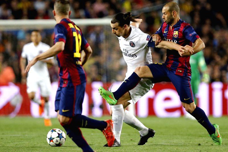 Barcelona's Javier Mascherano (R) vies for a ball with Paris Saint-Germain's Zlatan Ibrahimovic (C) during their UEFA Champions League quarter-finals second leg ...