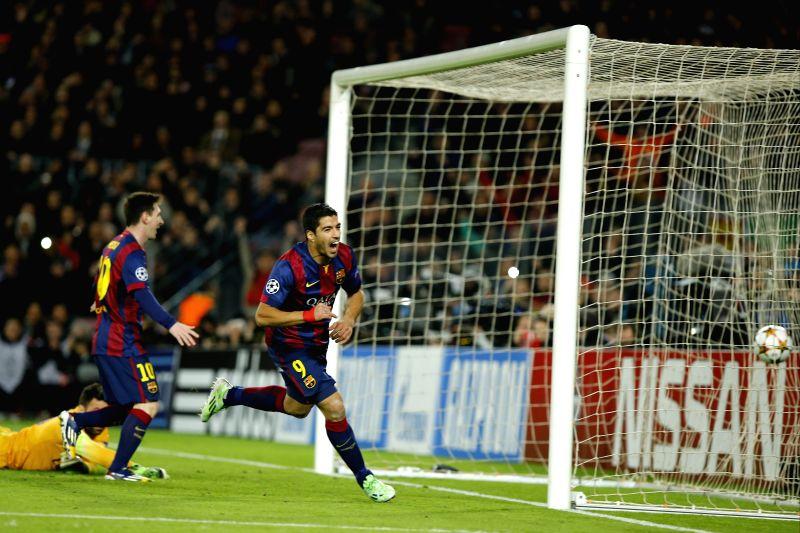 Barcelona's Luis Suarez (R) celebrates scoring during the UEFA Champions League group F football match against Paris Saint-Germain in Barcelona, Spain, on Dec. 10, 2014. Barcelona won 3-1.