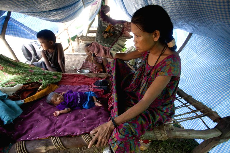 A woman takes care of her child under a shelter after flood in Bardiya, Nepal, Aug. 22, 2014. The death toll from floods in the northern Indian state of Uttar ...