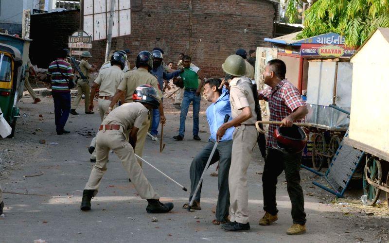 Baroda : Policemen charge batons after violence broke out during a Baroda Municipal Corporation demolition drive  on May 31, 2016.