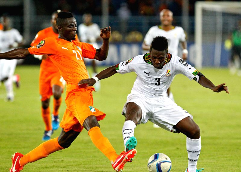 Asamoah Gyan (R) of Ghana vies with Eric Bertrand Bailly of Cote d'Ivoire during the final match of Africa Cup of Nations in Bata, Equatorial Guinea, Feb. 8, 2015. Cote