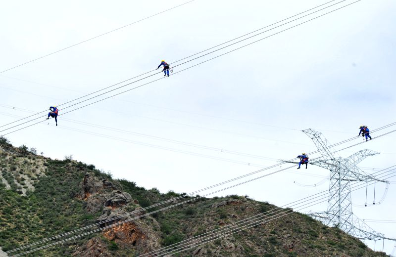 Batang (China): Photo take on Aug. 5, 2014 shows workers of the State Grid stringing electrical wires in Batang County, southwest China's Sichuan Province. China launched the transmission of power ...