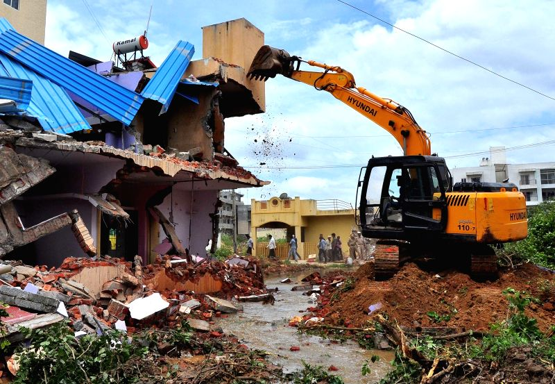 BBMP officials demolished houses encroached on Rajakaluve (drainage) at Arakere Ward by government order, to give way for the drainage system, which was flooded due to the recent rains, in ...