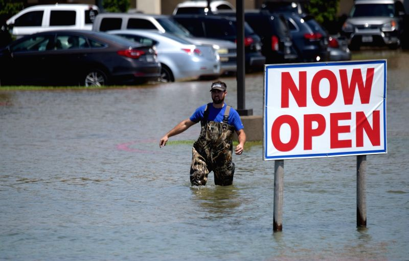 BEAUMONT (U.S.), Aug. 31, 2017 A man walks in a flooded parking lot in Port Arthur, Texas, the United States, Aug. 31, 2017. Nearly 40 people died or are feared dead in flooding or ...