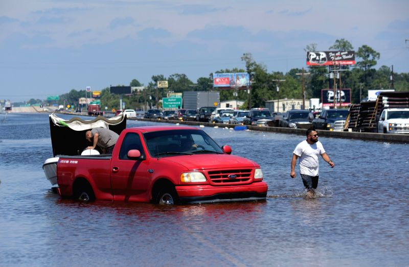 BEAUMONT (U.S.), Aug. 31, 2017 People and vehicles are seen on a flooded highway in Beaumont, Texas, the United States, Aug. 31, 2017. Nearly 40 people died or are feared dead in flooding ...