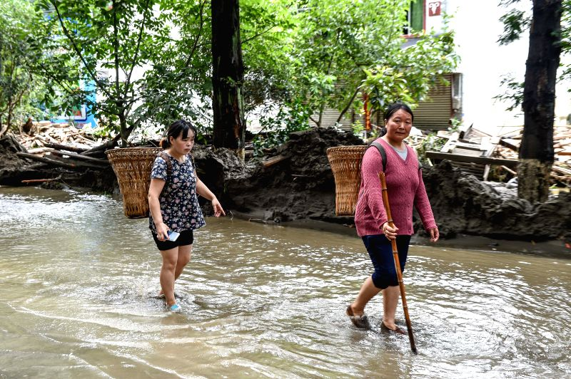 BEICHUAN, July 12, 2018 - Villagers wade through water on the street after the flood in Chenjiaba Town of Beichuan County, southwest China's Sichuan Province, July 12, 2018. Lasting torrentials in ...