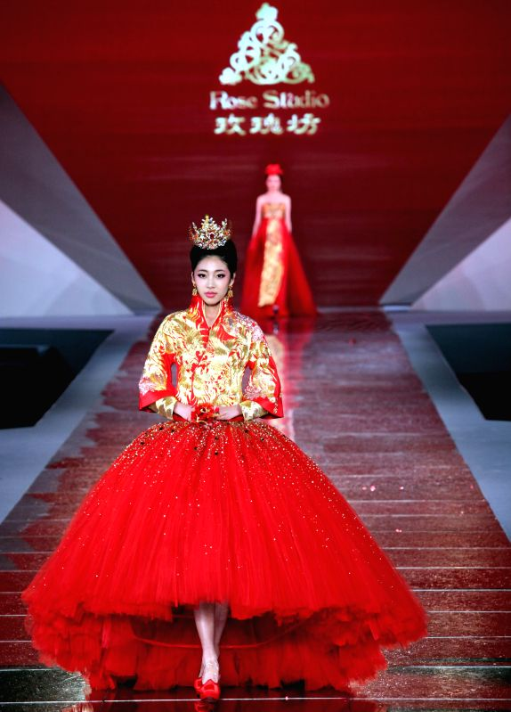 A model presents a creation designed by Guo Pei, a fashion designer winning the awards of China Fashion Meritorious People, during the awarding ceremony of China ...