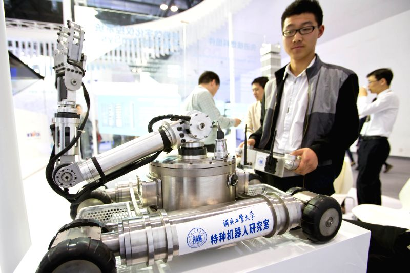 """A staff member demonstrates a nuclear detection robot at the exhibition """"Nuclear Industry China 2014"""" in Beijing, China, April 15, 2014. The four-day ..."""