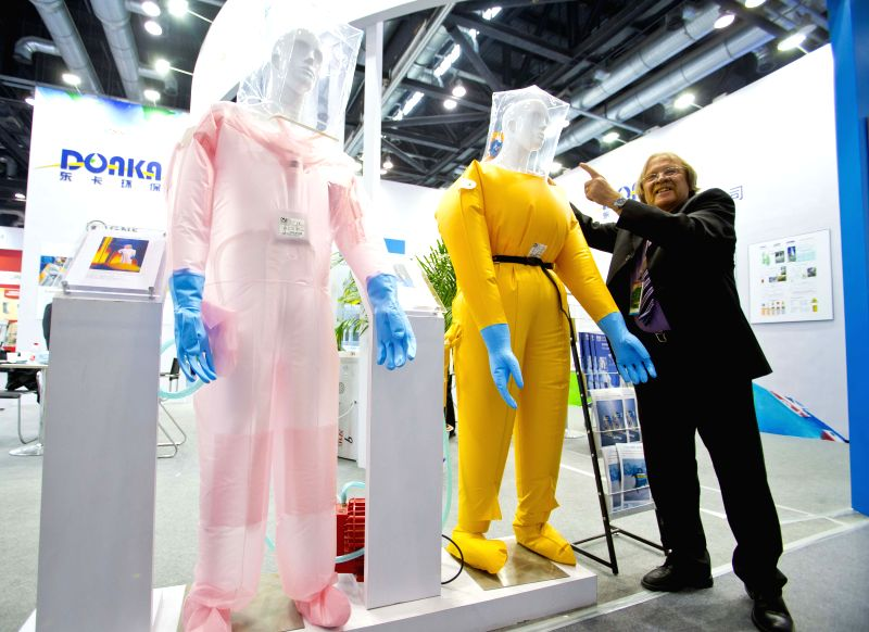 """A staff member shows protective suits at the exhibition """"Nuclear Industry China 2014"""" in Beijing, China, April 15, 2014. The four-day exhibition kicked .."""