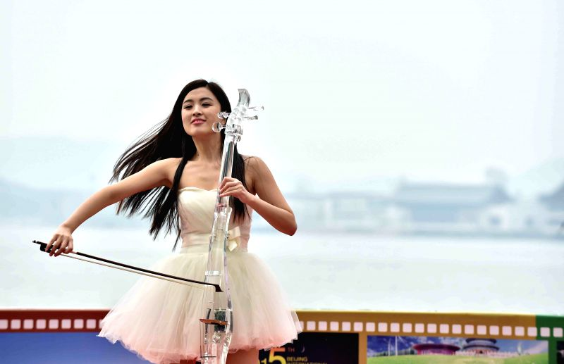A musician performs at the opening ceremony of the film carnival prior to the Beijing International Film Festival at the Yanqi Lake scenic area in Beijing, capital ...