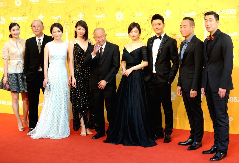 "Director John Woo (C) poses for photos on the red carpet with actors and actresses starring in the movie ""The Crossing"" at the opening ceremony of the ..."