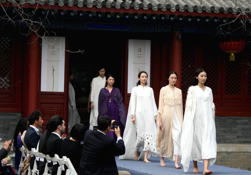 Models present creations of Qing's during its fashion show in Beijing, capital of China, April 18, 2015. The brand Qing's was established in Thailand in 2012. ...