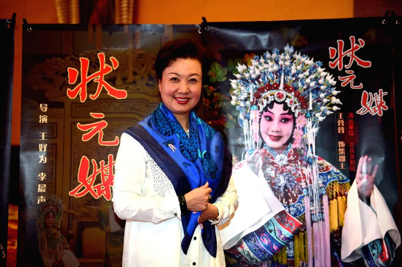 """Wang Rongrong, leading actress of Peking Opeara film """"The Pearl Shirt"""", poses for photo with the film's poster during the fifth Beijing International ..."""