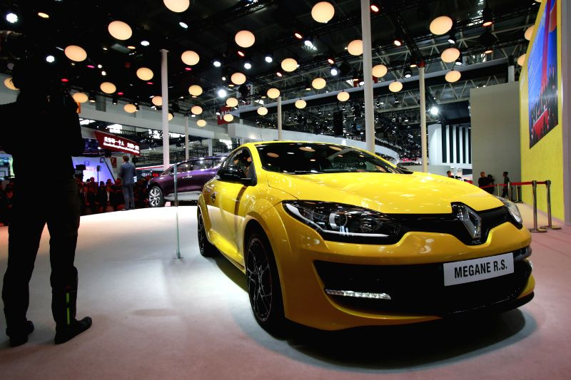 A journalist films a Renault  Megane car during the media preview of the 2014 Beijing International Automotive Exhibition in Beijing, China, April 20, 2014. The ...