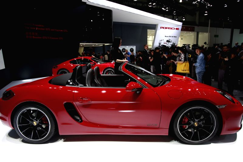 People view Porsche automobiles during the media preview of the 2014 Beijing International Automotive Exhibition in Beijing, China, April 20, 2014. The auto show ..