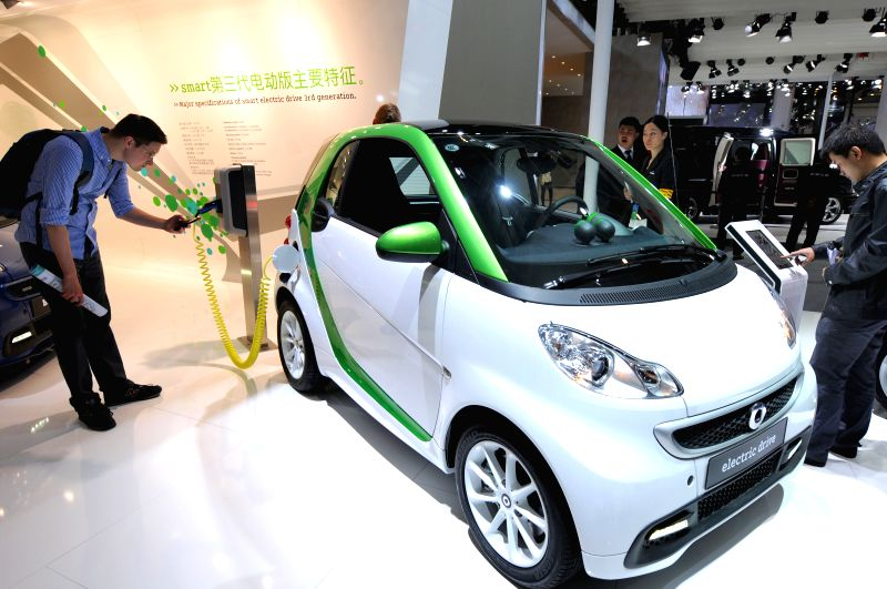 Visitors view an environmentally friendly electric car during the 2014 Beijing International Automotive Exhibition in Beijing, China, April 21, 2014. The auto show