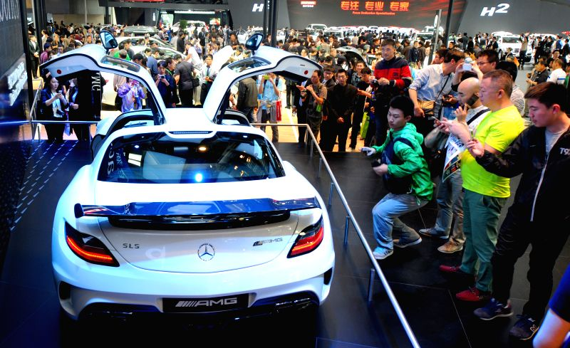 Visitors view the displayed automobiles during the 2014 Beijing International Automotive Exhibition in Beijing, China, April 21, 2014.  The auto show will be held .