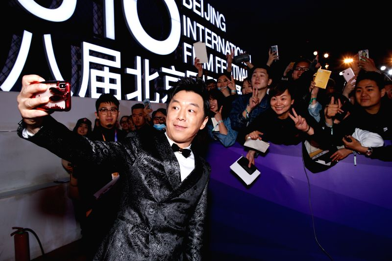 BEIJING, April 22, 2018 - Actor Huang Bo poses for selfie with audience on the red carpet for the closing ceremony of the 8th Beijing International Film Festival (BJIFF) in Beijing, capital of China, ... - Huang B